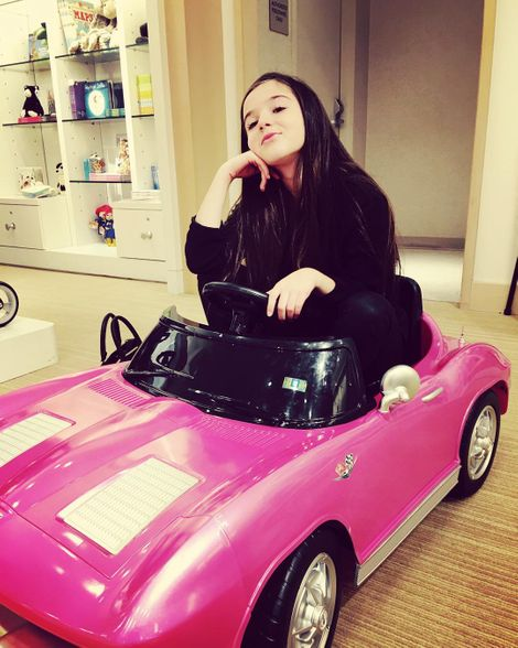 Alexa Nisenson driving her toy car