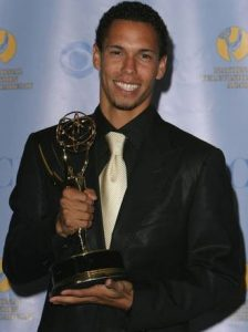 Bryton James holding a Daytime Emmy Award.
