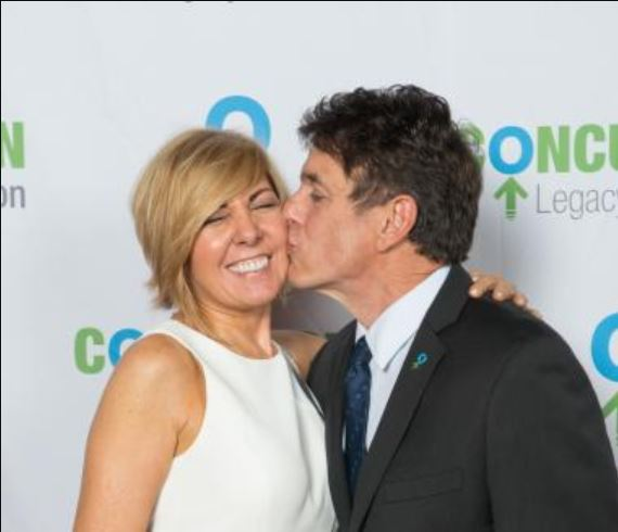 Mike Adamle kissing his ex-wife, Kim Adamle.