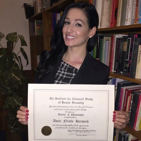 Amie holding her doctorate degree.