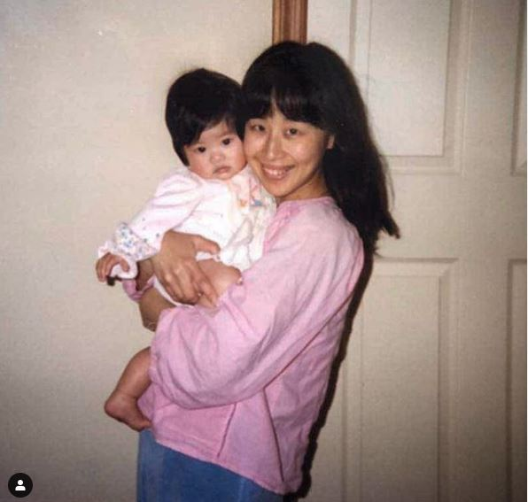 Childhood photo of Melody Peng in her mother's arm.