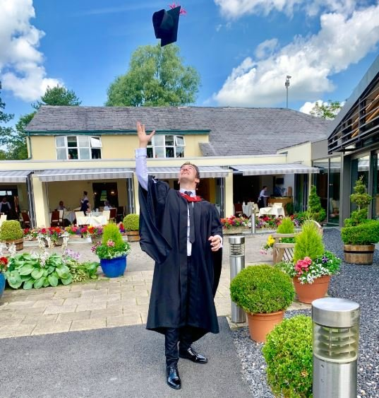 Cometan celebrating his graduation with his scholar's hat in the sky.