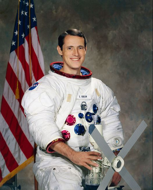 Photo of Edward Gibson holding a model in his white spacesuit.