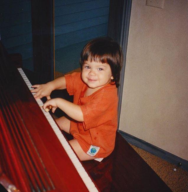 Childhood photo of Wolfgang Van Halen playing the piano.