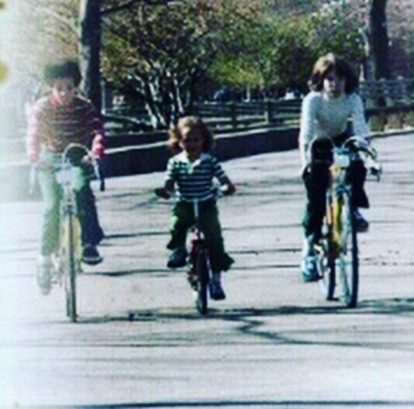 Childhood photo of Samantha Vincent cycling with her two big brothers, Paul (Left) and Tim (Right).