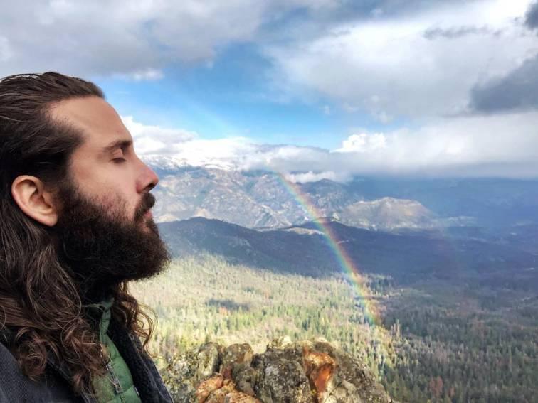Avi Kaplan is enjoying the beautiful scenery with a flowing rainbow.