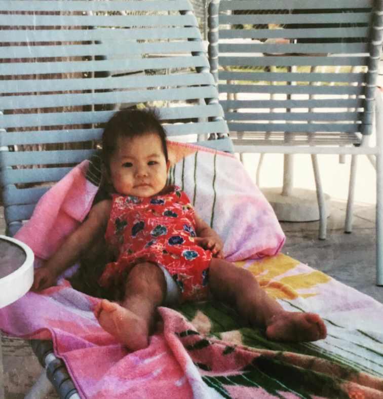 Childhood photo of Nicole Kang laying on the chair.