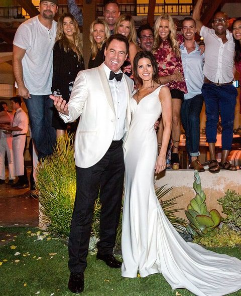 Mark Steines (left) with his wife Julie Steines (right) at their wedding with their guests at the back