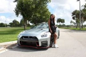 Naomi posing in front of her Bently.