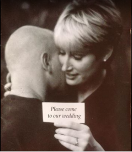 Travis's wife Kim holding a card where she is inviting her relatives to their wedding.
