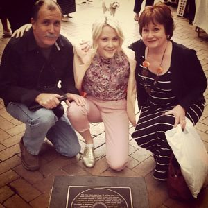 Emma taking picute with her parents