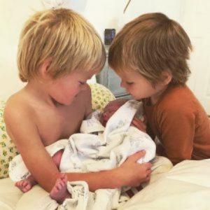 Sasha blue Pownall (left) holding her newly born brother.