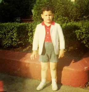 Young Isaac wearing a white blazer over red shirt with gray shorts