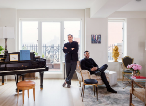 Isaac Mizrahi (standing up) and his husband (in a sofa) in their NYC apartment