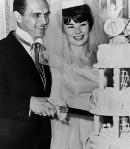 Newly wed Newhart couple cutting their wedding cake.