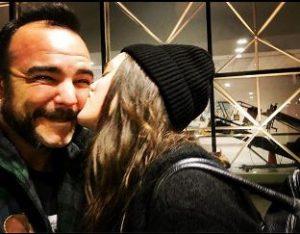 Julia kissing on the cheek of Samuel Herring