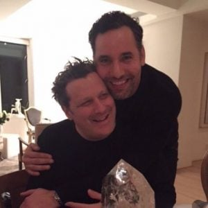 Arnold Germer hugs his smiling partner, Isaac Mizrahi from back as they pose for a picture