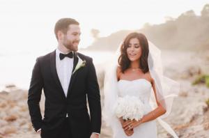 Sazan Hendrix in a wedding gown beside her husband Stevie Hendrix, holding flowers.