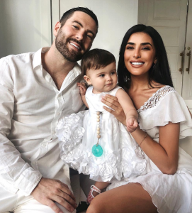 Sazan Hendrix with her husband Stevie Hendrix and daughter Valentina taking a family picture in white dress.