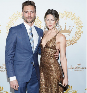 Andrew Walker wearing blue suit with his wife Cassandra wearing golden dress