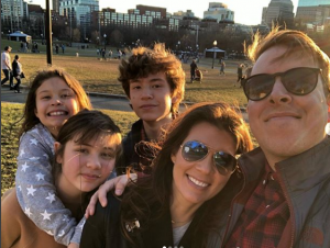 Erika with her husband and three children hanging out.